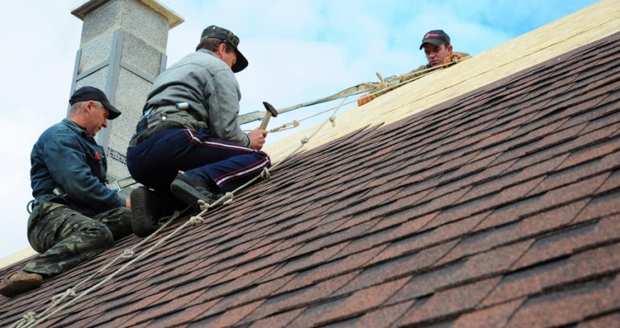 KIEV - UKRAINE MAY - 8  2017: Roofing Construction. Roofing Contractors Install New House Roofing with Asphalt Shingles Roofing Construction. Roofers with safety rope. Roofing Contractor.